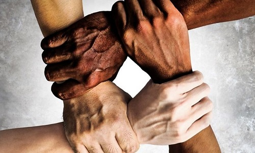 Multiracial hands holding each others wrists.