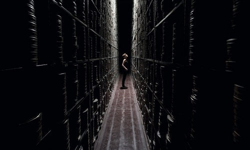 A woman stood in a darken hallway of stacked movie reel containers.