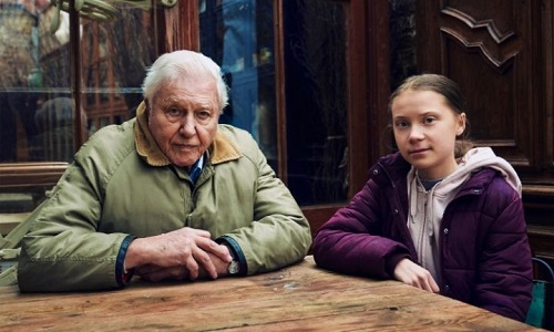 Sir David Attenborough and Greta Thunberg sit side by side at a table (photo credit: Alex Board)