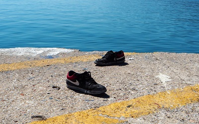 Two shoes lie next to the sea on the island of Lesbos, Greece