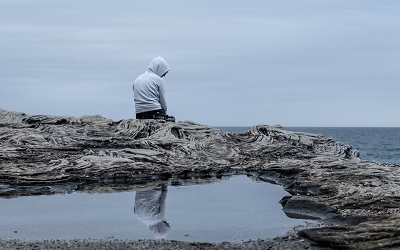 Young male sits on the edge of a rock on a beach looking deep in thought