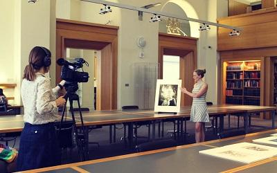 Photo of Dr Leah Clark being filmed in the Victoria and Albert museum, London