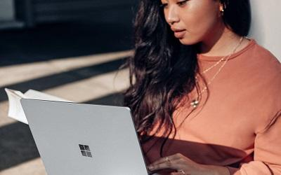 A female with long dark hair using a laptop