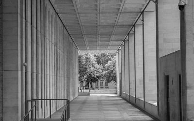 Photo by Jeremy Segrott - photo is black and white and shows a long corridor in the Welsh Government Building, Cardiff, taken 2016. At the end are trees.