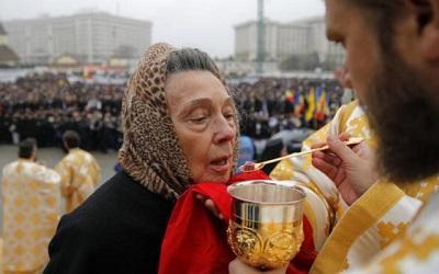 Romanian lady taking communion