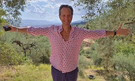 Actor Richard E Grant with arms outstretched