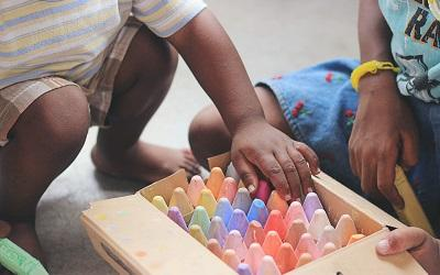 Photo by Tina Floersch on Unsplash - image shows the hands of two small children reaching into a colourful box of chunky chalks